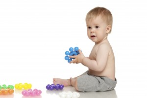 Baby playing with colorful toys on the floor, over white background