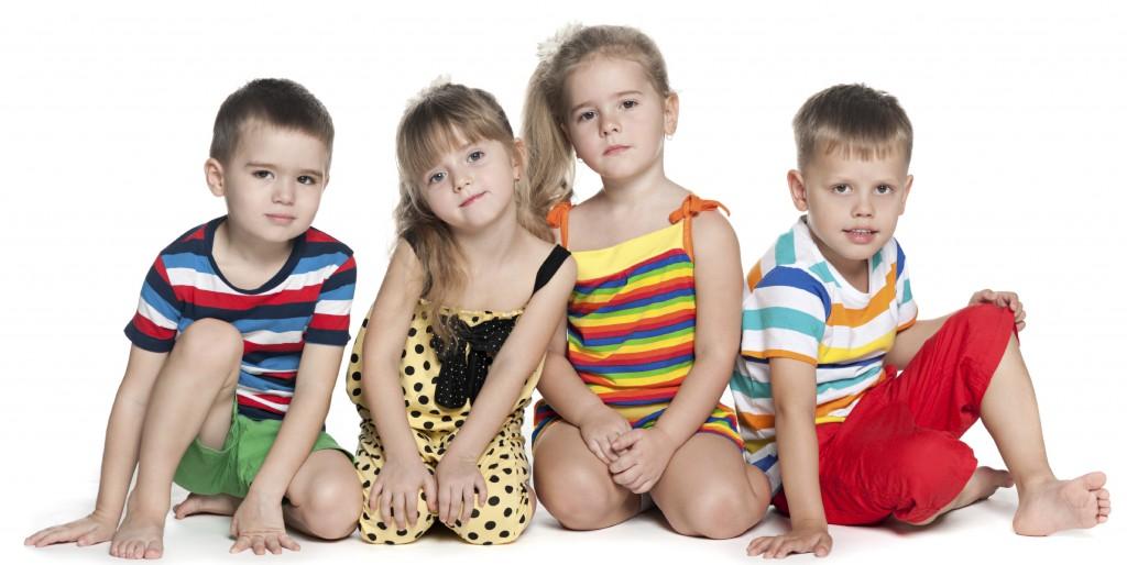 Four preschool children sit on the floor