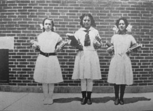 These girls demonstrate the healthy practice of carrying equal weight in each arm to avoid distorting the spine. 1913