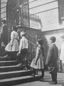 School children being evaluated for posture flaws while walking up stairs. 1913.