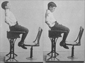 A boy performing sit-ups at his desk to improve his core strength and posture.