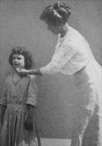 A girl has her head positioning corrected by a school teacher. 1913.